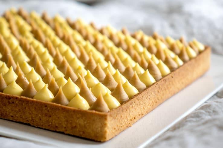 Recette de la tarte passion Dulcey. Elle se compose d'une pâte sucrée, d'un croustillant gianduja, d'un crémeux au fruit de la passion et d'une ganache au Dulcey.